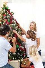 Composite image of joyful family decorating christmas tree