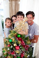 Composite image of happy family decorating a christmas tree