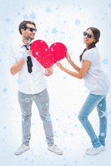 Hipster couple smiling at camera holding a heart