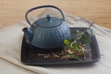 Teapot with tea branch and leaves