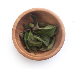 Dried tea leaves in wooden bowl