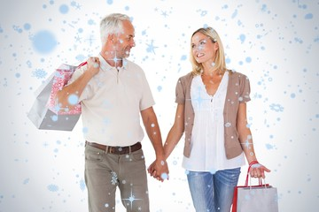 Happy couple holding shopping bags and hands