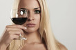 Beautiful blond woman with red wine.look in glass.drink