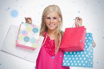 Smiling blonde showing shopping bags