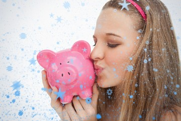 Close up of a young woman kissing a piggybank