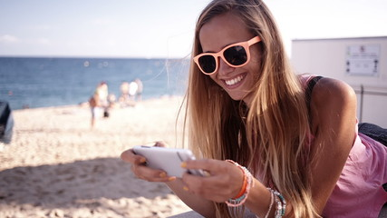 Girl with sunglasses texting on phone