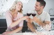 Composite image of couple toasting red wine glasses at table
