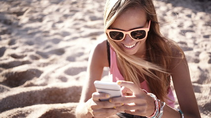 Girl sits on beach and messages on her phone