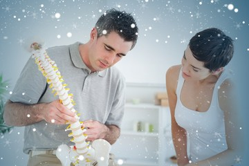 Chiropractor and patient looking at a model of a spine
