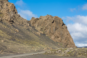 Track and rock hill through Iceland, blue sky