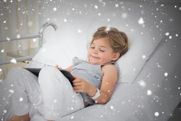 Composite image of little sick girl using digital tablet