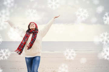 Woman in warm clothing stretching arms on beach