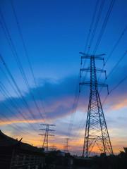 high voltage power pylons in sun set