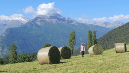 farm girl with pitchfork in an alpine landscape