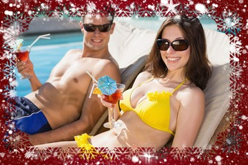 Smiling couple with drinks sitting by swimming pool