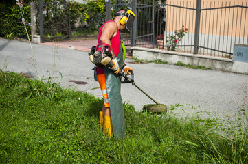 Man cutting grass with petrol mower