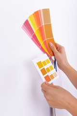 Woman choosing color for wall from swatches in room