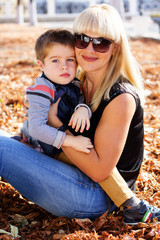 Little toddler boy in autumn park with his mother