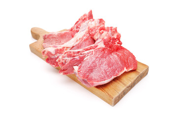 Three raw beefsteaks on a wooden cutting board