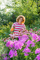 pretty woman looks after behind plants in garden