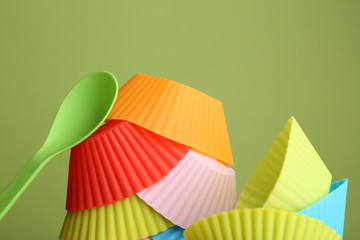Plastic bowls and spoon on color background