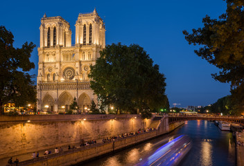 Notre Dame cathedral at dusk with blurred boat lights over Seine