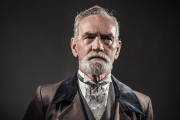 Vintage characteristic senior man with gray hair and beard. Stud