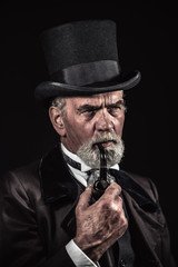 Pipe smoking vintage victorian man with black hat and gray hair