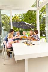 Familie sitzt am Tisch beim Mittagessen