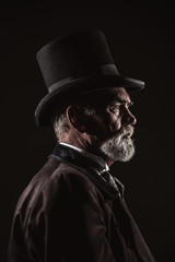 Vintage victorian man with black hat and gray hair and beard. St