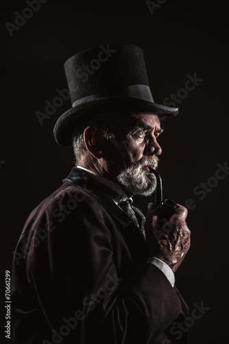 Pipe smoking vintage victorian man with black hat and gray hair - 70661299