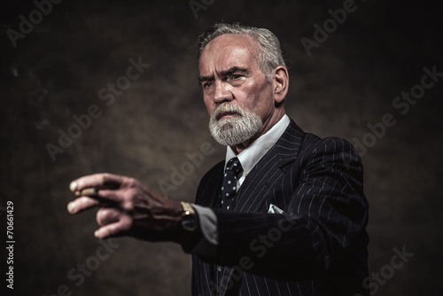 Cigar smoking characteristic senior business man with gray hair - 70661429