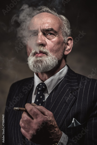 Cigar smoking characteristic senior business man with gray hair - 70661461
