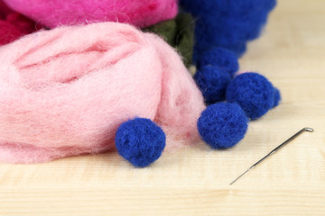 Wool for felting with needle on wooden background
