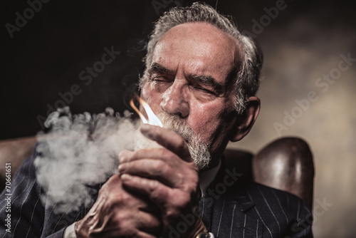 In chair sitting characteristic senior business man. Smoking cig - 70661651