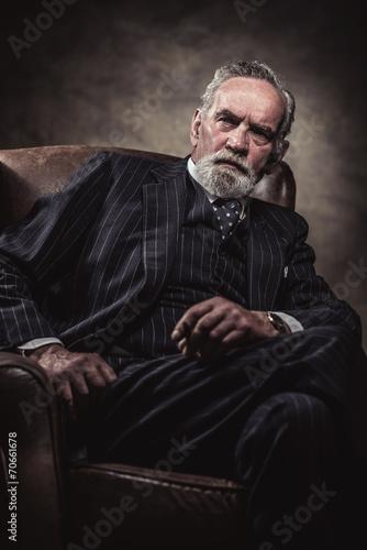 In chair sitting characteristic senior business man. Smoking cig - 70661678