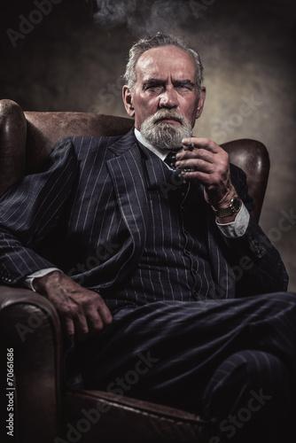 In chair sitting characteristic senior business man. Smoking cig - 70661686