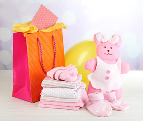 Baby clothes and gift bag on bright background