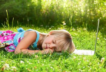 Child sleeping on computer outdoor