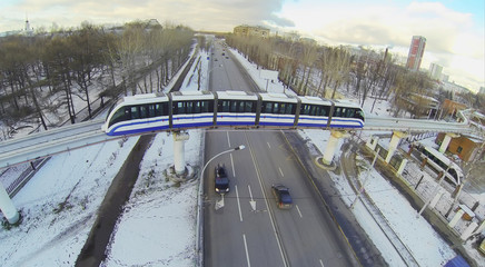 Monorail train passes over a four-lane road in the city
