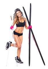 Smiling athletic woman in hat, gloves with skis and ski poles in