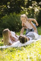 Vater liegt auf Rücken hält Tochter im Luft im Garten