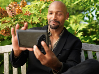 mature african taking selfie with smartphone