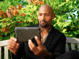 mature african man using tablet outdoors