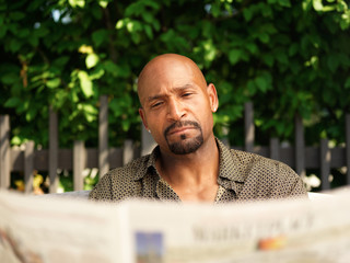 mature african american man reading newspaper