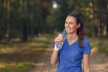 Sportliche junge Frau trinkt aus einer Wasserflasche