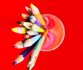 Colour pencils isolated on red background close up
