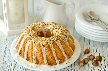 Glazed cake with hazelnuts on white background