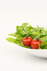 schüssel mit rucolasalat und tomaten