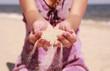 Female hands sypyat sand on the seashore